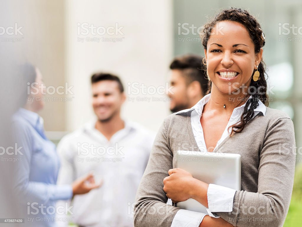 Happy African American businesswoman holding touchpad outdoors. stock photo