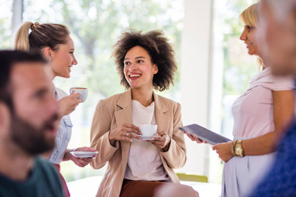 Happy African American businesswoman talking to her colleagues on a coffee break at casual office. stock photo