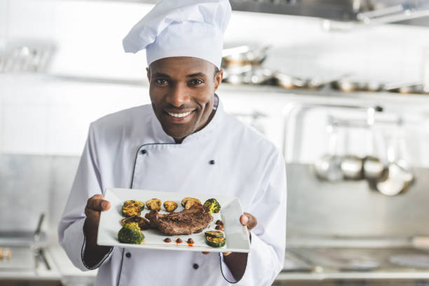 Happy african american chef holding plate with cooked steak and at picture id941469070?b=1&k=6&m=941469070&s=612x612&w=0&h=4ghirz7vyveqacxvud0vpv wfsa3dkyotigrhh3ewq8=