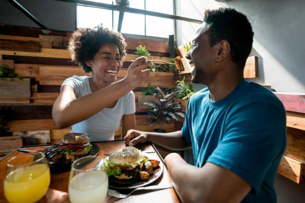 Heureux couple afro-américain à un restaurant et une femme à nourrir son petit ami - Photo