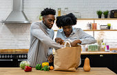 istock Happy African American couple at home unpacking the groceries 1206327629