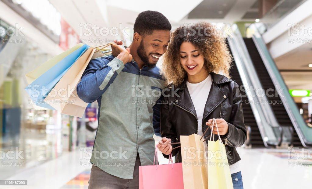 Glücklich es, afrikanisches amerikanisches Paar, das über Einkäufe und Lächeln diskutiert - Lizenzfrei Afrikanischer Abstammung Stock-Foto