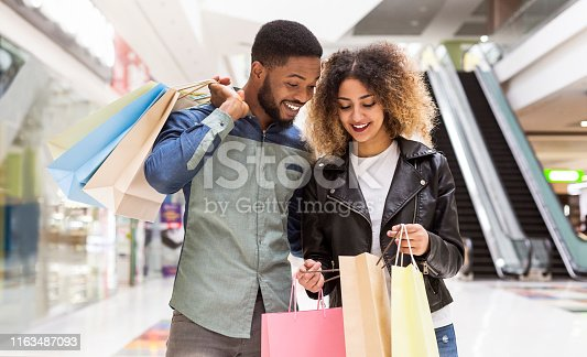 Happy african american couple discussing purchases and smiling, panorama