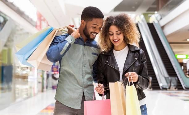 幸せなアフリカ系アメリカ人のカップルが購入と笑顔について話し合う - ショッピングセンター ストックフォトと画像