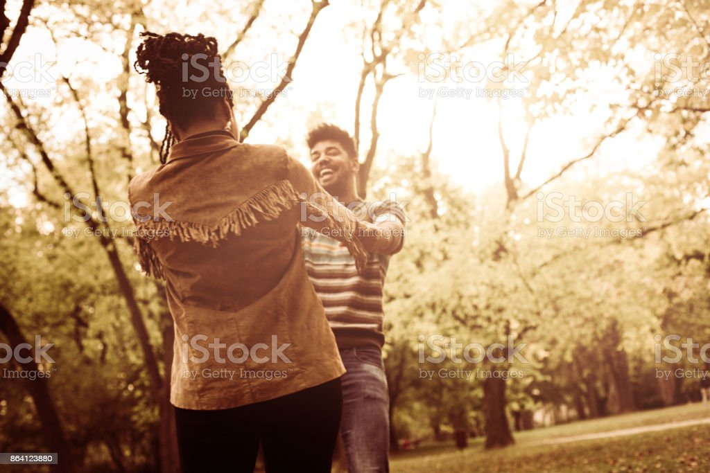 Happy African American couple in park holding hands and rotate in circle. royalty-free stock photo