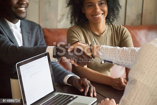 istock Happy african american couple making deal handshaking caucasian broker, closeup 914989724