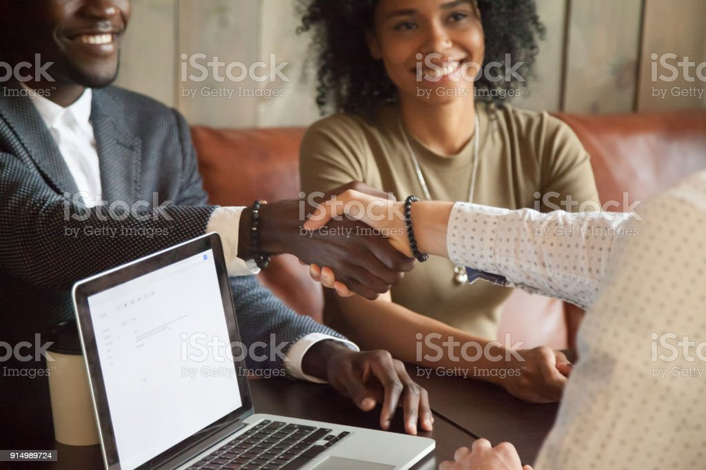 Happy african american couple making deal handshaking caucasian broker, closeup stock photo
