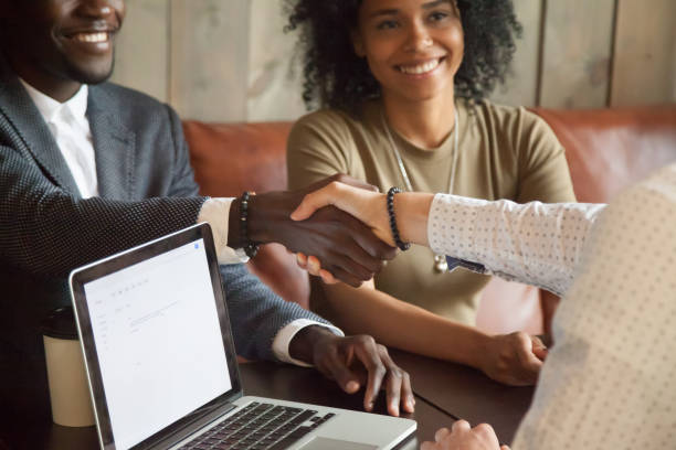Happy african american couple making deal handshaking caucasian broker, closeup Happy young african american couple making deal handshaking caucasian insurance broker in cafe, black satisfied customer and realtor or sales person shaking hands at meeting in office with laptop mortgage loan stock pictures, royalty-free photos & images