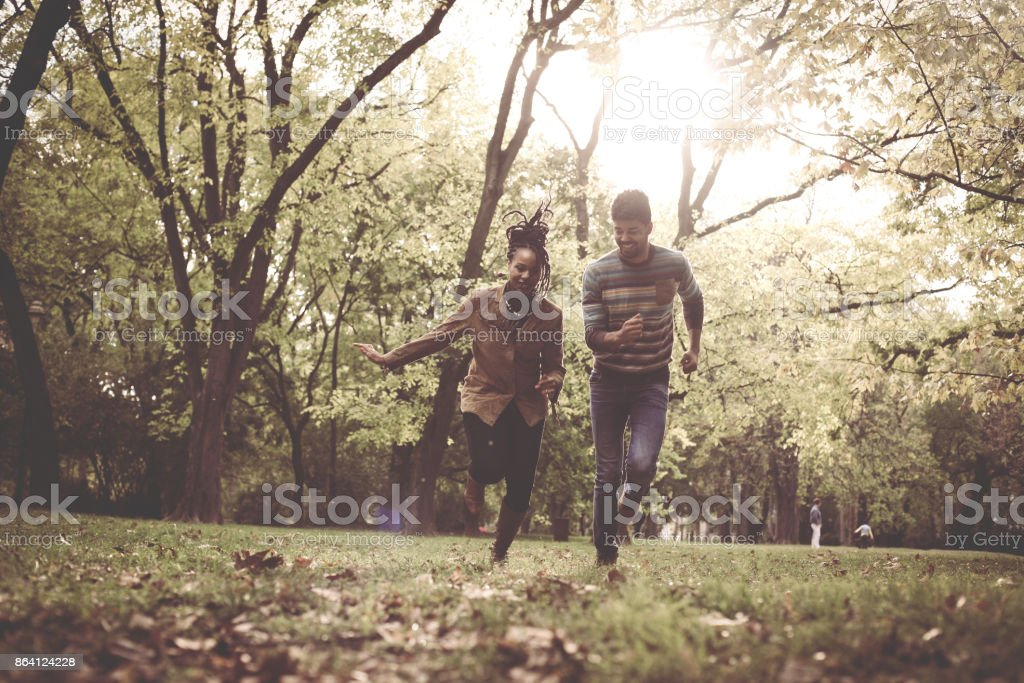 Happy African American couple running and catching in park. royalty-free stock photo