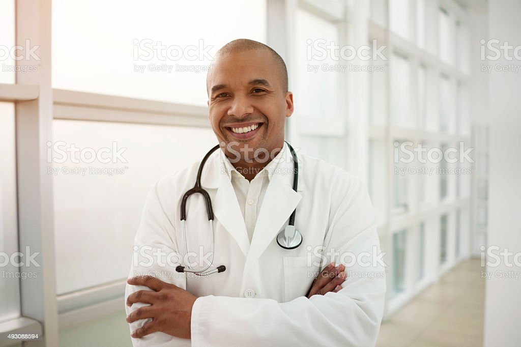 Happy African American doctor standing with his arms crossed. stock photo