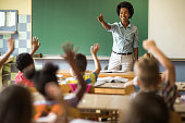 Happy African American elementary teacher aiming at school kid to answer her question.