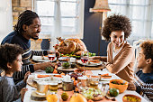 Happy black family talking during Thanksgiving meal at dining table.