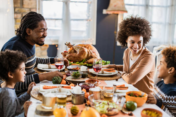 happy african american family communicating while having thanksgiving lunch in dining room. - thanksgiving dinner zdjęcia i obrazy z banku zdjęć