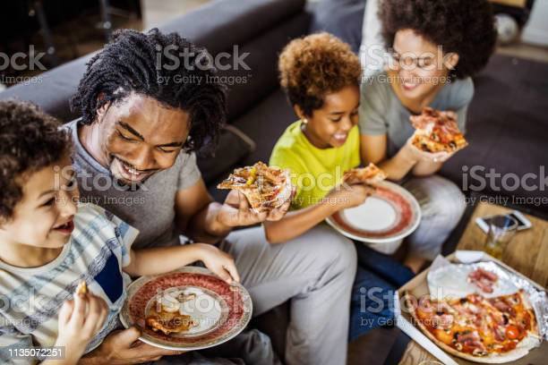Happy african american family eating pizza at home picture id1135072251?b=1&k=6&m=1135072251&s=612x612&h=m gaznaphc8ipam3jlzsft92 t0atc8hiwoz2wyiugm=