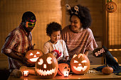 Happy African American family enjoying in Halloween at home.