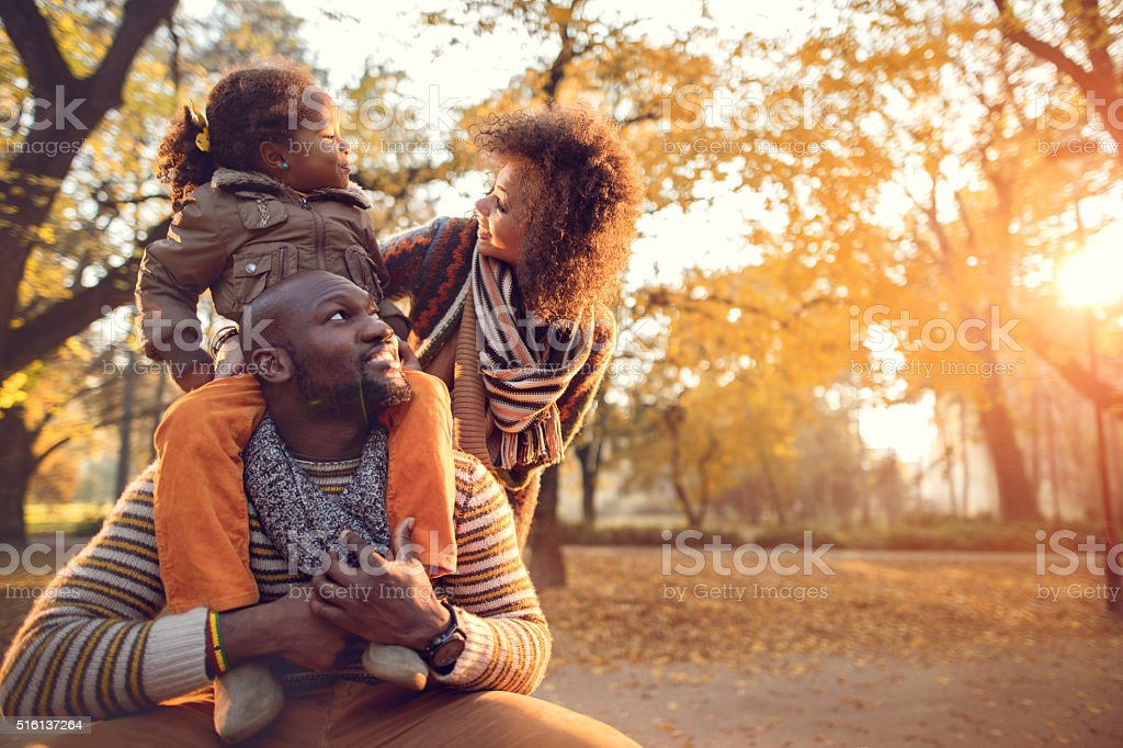 Happy African American family enjoying in nature during autumn. stock photo