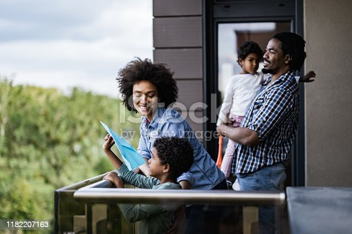 Happy black parent and their small kids enjoying on a terrace of their apartment. Focus is on woman.