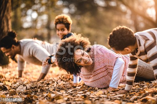 Happy black family doing push-ups in autumn leaves at the park. Focus is on woman.