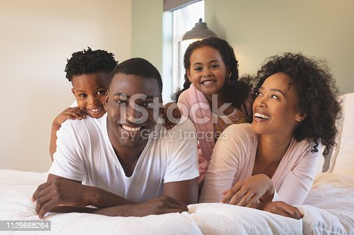 istock Happy African American family lying on bed and looking at camera 1129668264