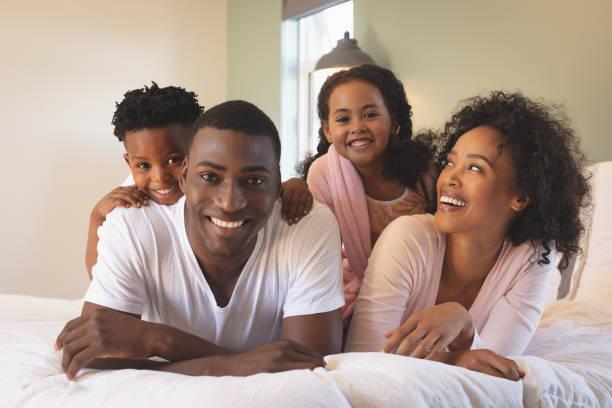Glücklich afroamerikanische Familie liegen auf Bett und Blick in die Kamera – Foto