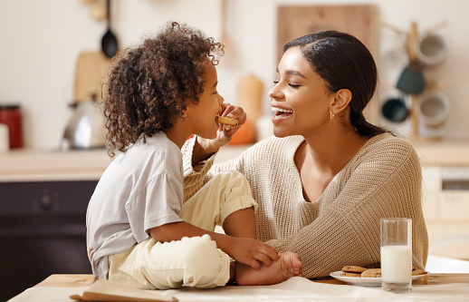 happy african american family: mother and little son eat cookies with milk for breakfast at home