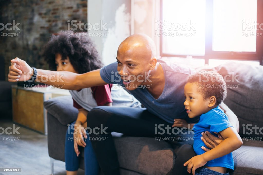 Happy African American family of three watching tv and cheering sport games on sofa at home stock photo