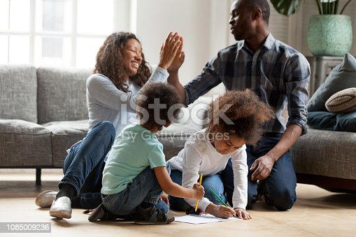 Happy African American family playing together indoors, adorable toddler son and littler preschooler daughter drawing with colorful pencils, smiling joyful wife and husband giving high five