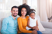 istock Happy African American family portrait sitting on couch at home. 540611372