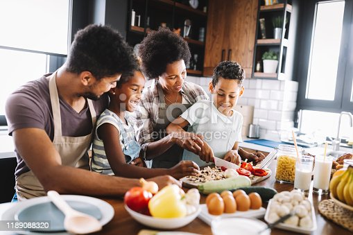 Happy african american family preparing healthy organic food together in kitchen