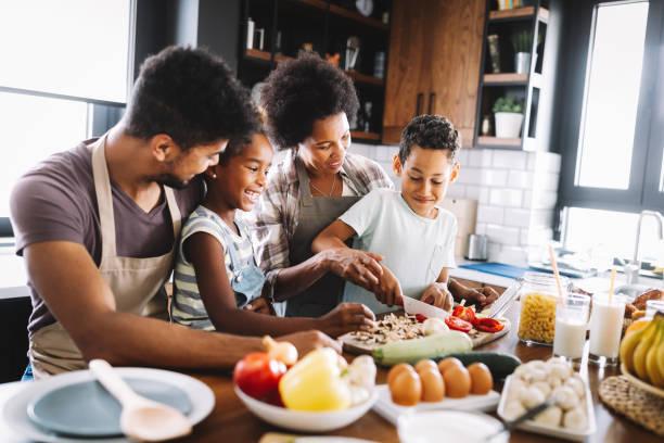 felice famiglia afroamericana che prepara cibo sano insieme in cucina - cucinare foto e immagini stock