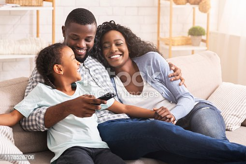 Smiling african american family relaxing on couch and watching TV at home, man switching channels