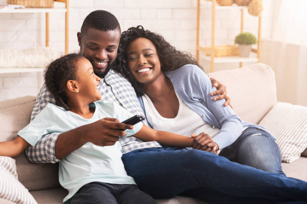 Happy african american family relaxing and watching TV at home Smiling african american family relaxing on couch and watching TV at home, man switching channels african american ethnicity stock pictures, royalty-free photos & images