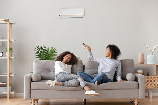 Happy african family relax on sofa under air conditioner, black mom holding remote control switch on conditioning in living room adjust comfort temperature for daughter, climate system at modern home