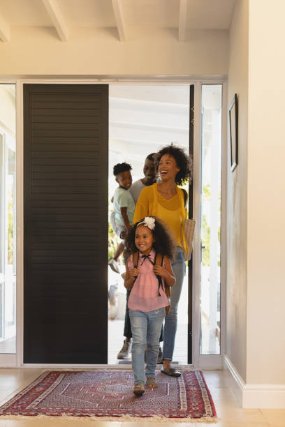 Happy African American family returning sweet home Front view of happy African American family returning sweet home entering stock pictures, royalty-free photos & images