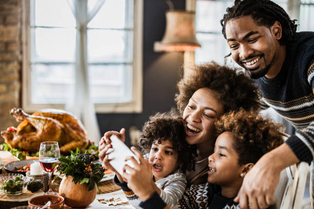 happy african american family taking a selfie during thanksgiving lunch. - eating technology stock pictures, royalty-free photos & images