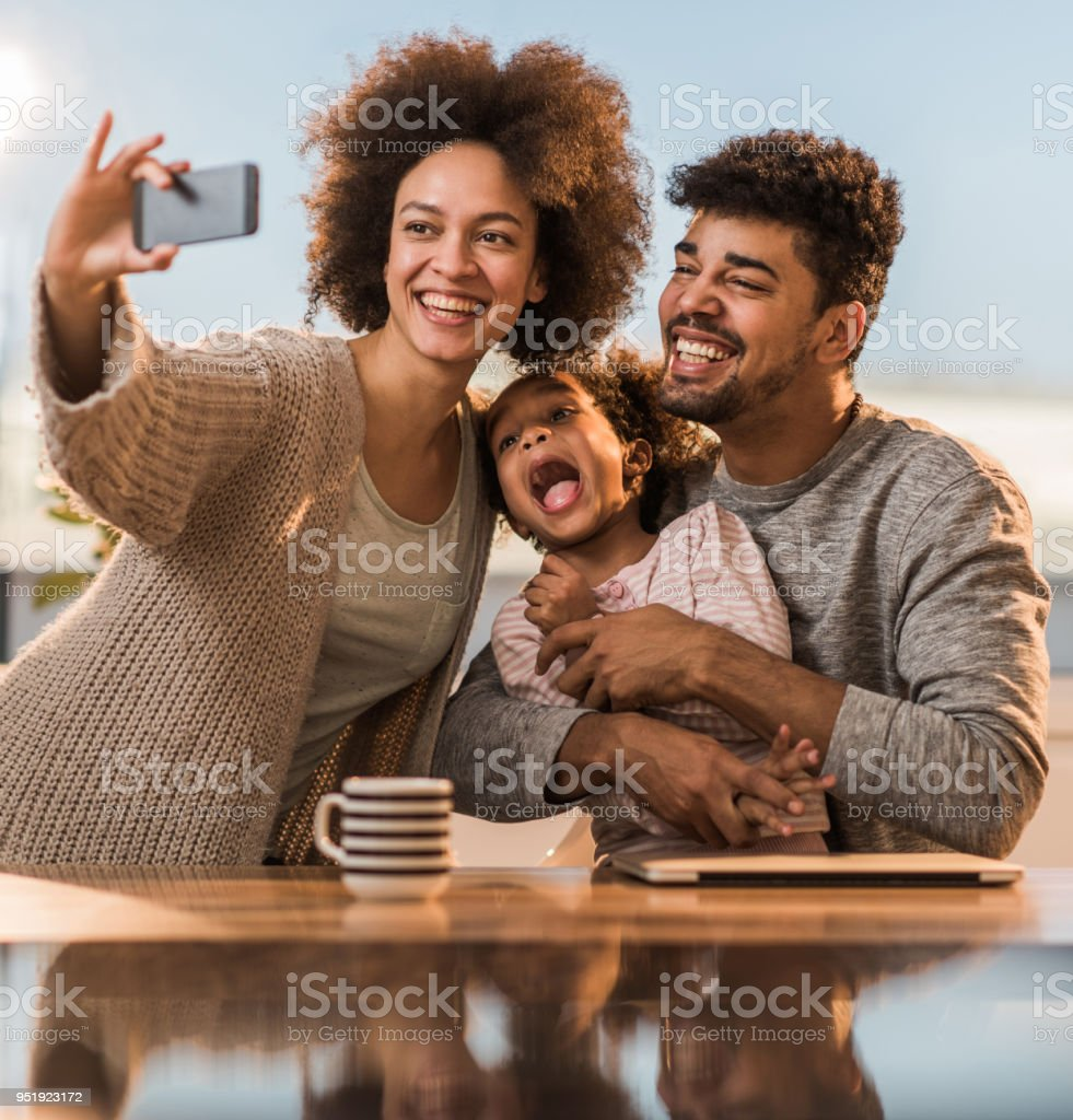 Young happy black family taking a selfie with smart phone while...