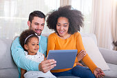 istock Happy African American Family using digital tablet at home. 540611196