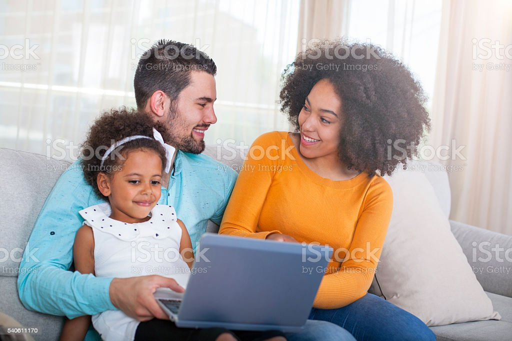 Happy African American Family using laptop at home. stock photo