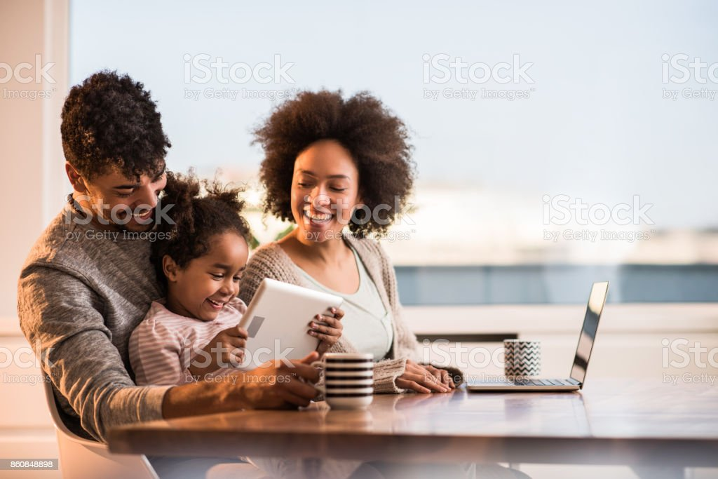 Happy African American family using wireless technology at home. stock photo