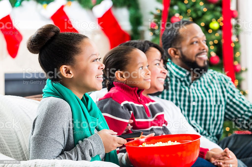 Happy African American family watch a Christmas movie stock photo