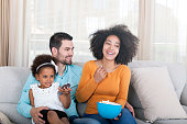istock Happy African American Family watching TV and eating popcorn 540611128