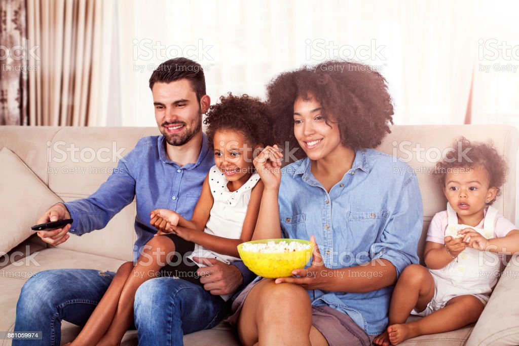 Happy African American Family watching TV and eating popcorn stock photo