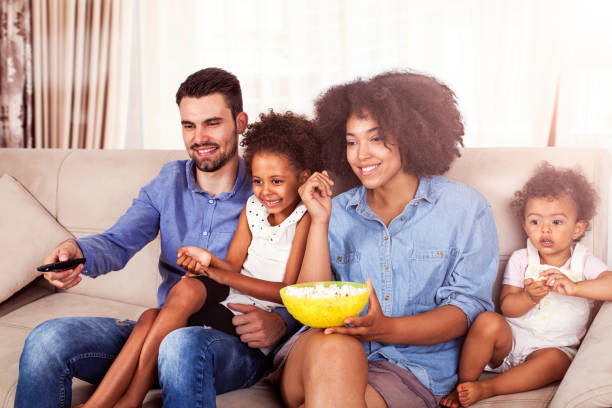 happy african american family watching tv and eating popcorn - family watching tv stock photos and pictures