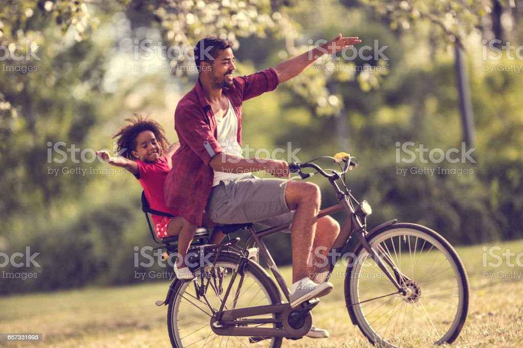 Happy African American father and daughter cycling in the park. stock photo