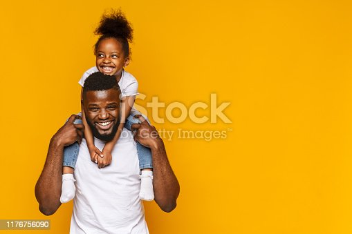 Happy african american father and daughter having fun, riding on shoulders, orange background with copy space