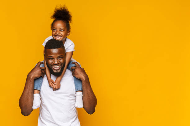 Happy african american father and daughter having fun Happy african american father and daughter having fun, riding on shoulders, orange background with copy space father stock pictures, royalty-free photos & images