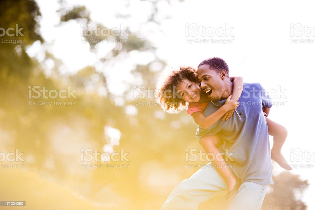 Happy African American father piggybacking his little girl outdoors. stock photo