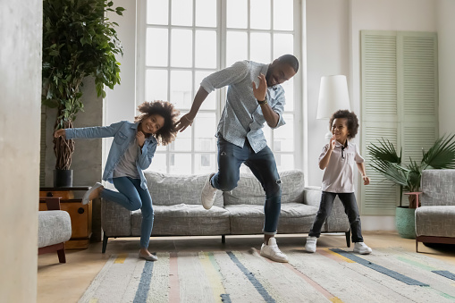 Happy african american father showing funny dancing moves to energetic small children siblings at home. Laughing crazy little biracial boy and girl having fun with caring daddy in living room.