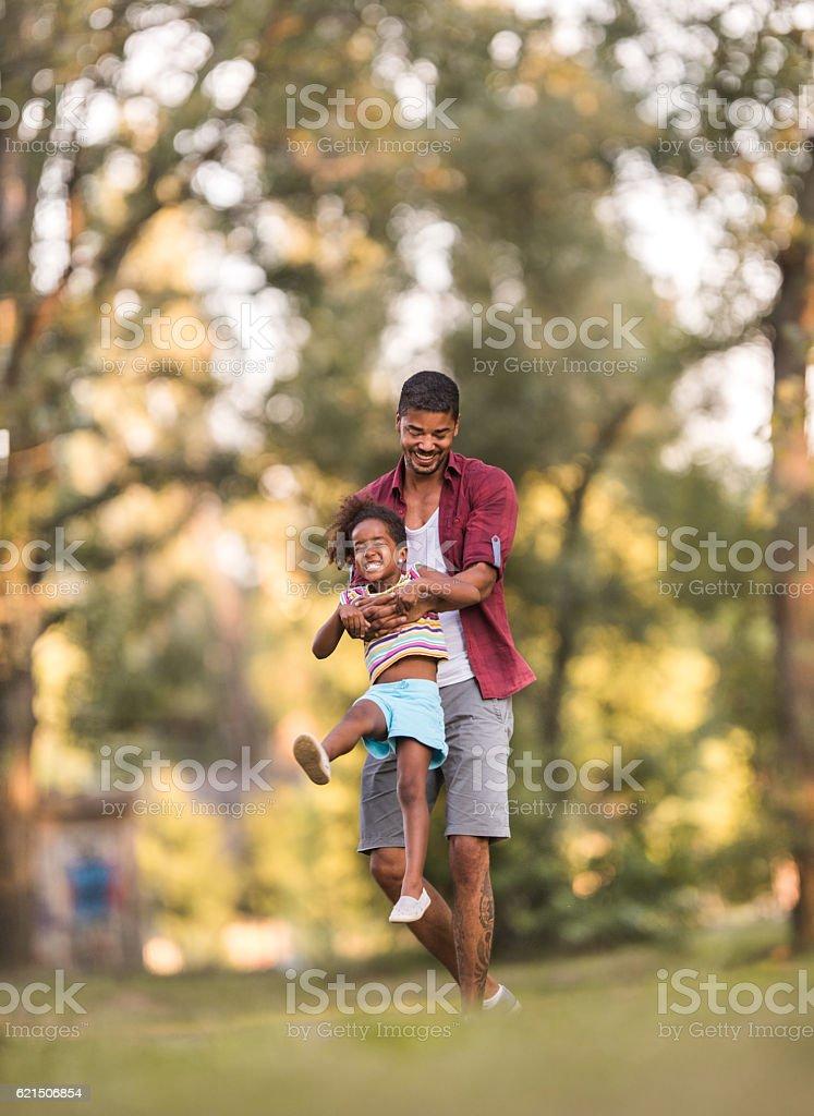 Glückliche afroamerikanischen Vater spinnen seiner Tochter im park. Lizenzfreies stock-foto