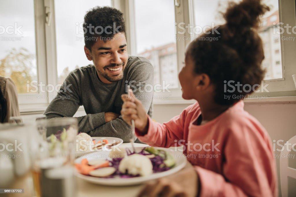 Glad African American Fader talar till sin lilla dotter under lunchen hemma. - Royaltyfri Afrikanskt ursprung Bildbanksbilder